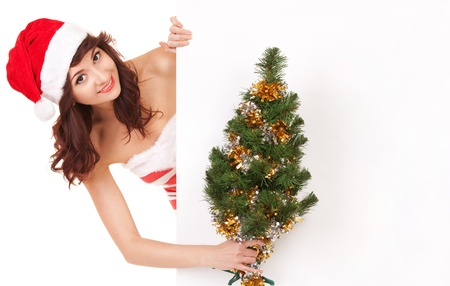 Santa woman with christmas tree peek behind the white blank board Stock Photo - 17038647