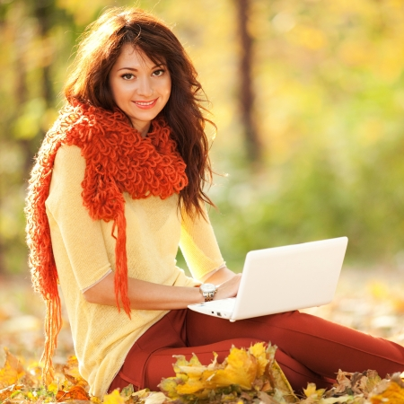 siting: Cute woman with white laptop in the autumn park