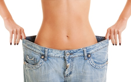 loose weight: Woman shows her weight loss by wearing an old jeans, isolated on white background