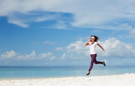 Jeune femme courant sur la plage