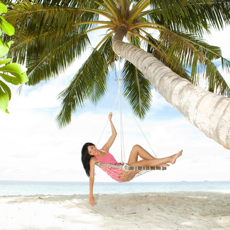 sea bed: Happy woman relaxing in hammock on a tropical beach Stock Photo