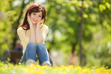 Young woman in the park with flowers photo