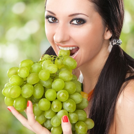 Pretty woman with grape on the green background photo