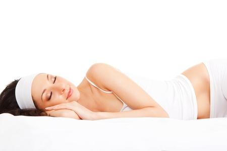 buonanotte: Carino donna dorme sul letto bianco