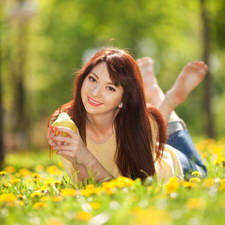 Happy woman with pear in the park photo