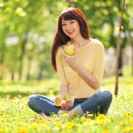 Happy woman eating fruits in the park photo