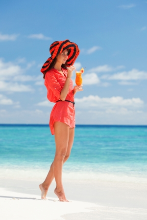 Fashion woman drinking cocktail on the beach photo