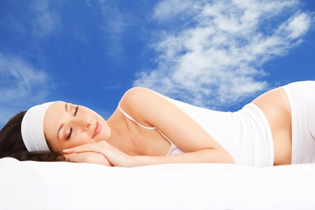 woman lying in bed: Cute woman sleeps on the white bed