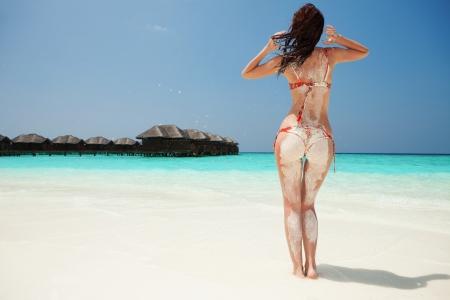 セクシーな女性は、夏のビーチでリラックスします。