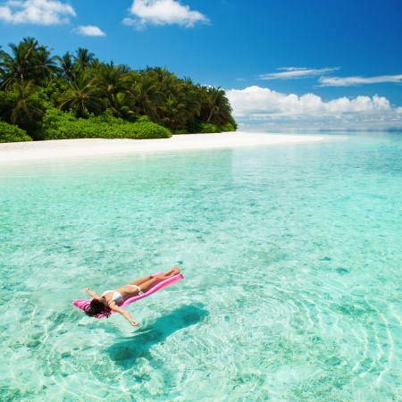 maldives beach: Woman relaxing on inflatable mattress in the sea Stock Photo