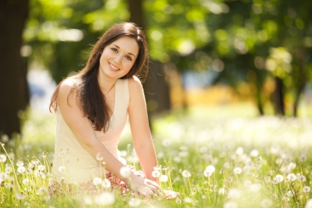 Cute woman rest  in the park with dandelions Stock Photo