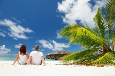 resort life: Happy couple sitting on the sunny beach