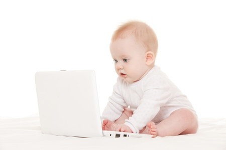 Cute baby with laptop on the white bed photo