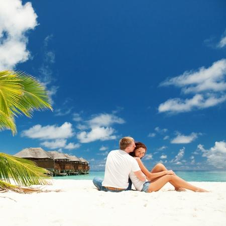 resort life: happy couple kissing in the sunny beach Stock Photo