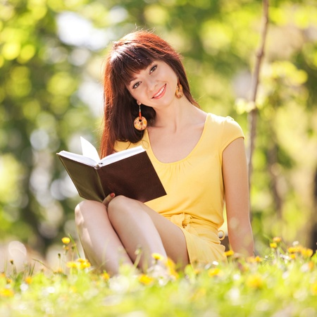 Young woman reading a book in the park with flowers photo