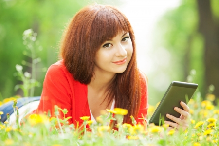 ereader: Happy woman with tablet in the park