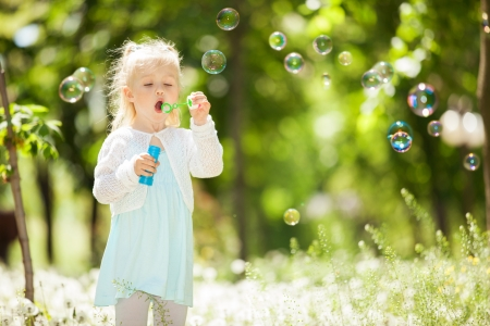 Cute little girl blowing bubbles in the park photo