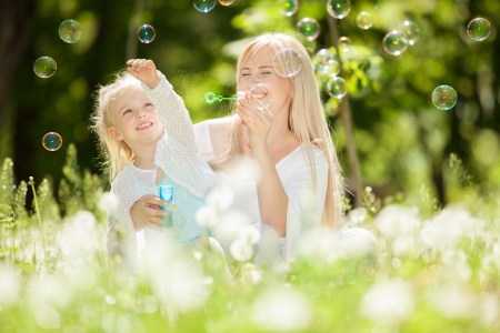 woman blowing: Happy mother and daughter blowing bubbles in the park