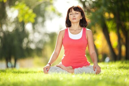 mantra: Pretty woman doing yoga exercises in the park