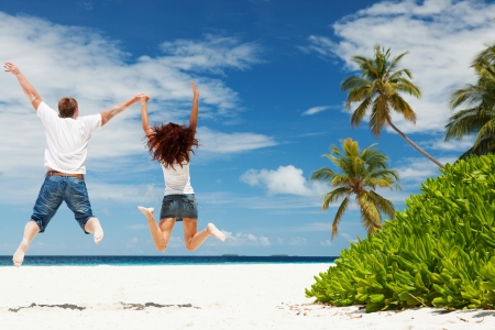 Happy couple jumping on the tropical beach photo