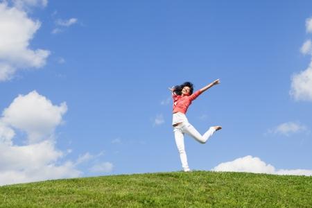 saludable: joven y bella mujer saltando sobre la hierba verde Foto de archivo
