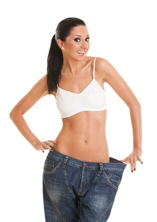 Funny woman shows her weight loss by wearing an old jeans, isolated on white background Stock Photo