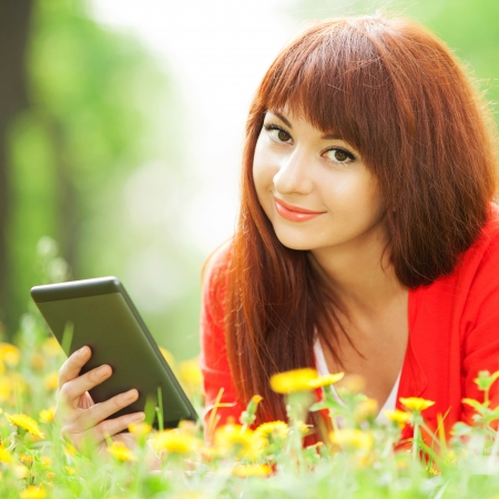 Happy woman with tablet in the park photo