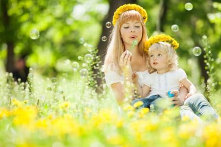 Gl?ckliche Mutter und Tochter bl?st Seifenblasen im Park Standard-Bild - 20991794