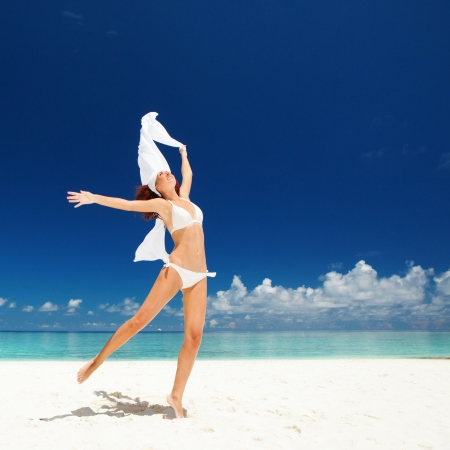 Happy young woman jumping on the beach photo