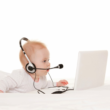 Cute baby-operator with laptop on the white bed photo