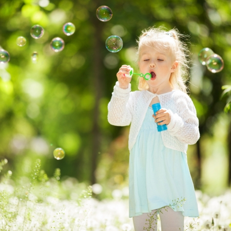 Cute little girl blowing bubbles in the park Stock Photo