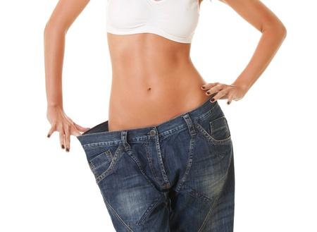 vrouw toont haar gewichtsverlies door het dragen van een oude spijkerbroek, op een witte achtergrond Stockfoto