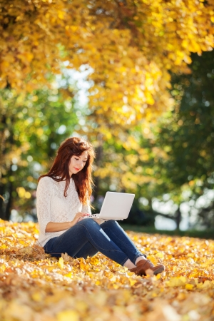 Cute woman with white laptop in the autumn park photo