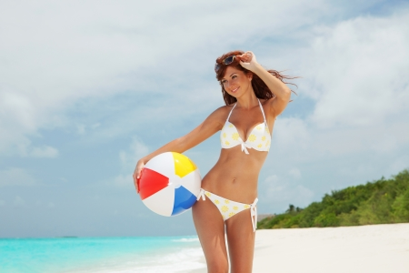 beach volleyball: Young pretty woman with ball on the beach background