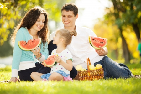 Happy family having a picnic in the autumn garden photo