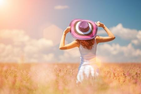 Woman in the field with flowers Foto de archivo