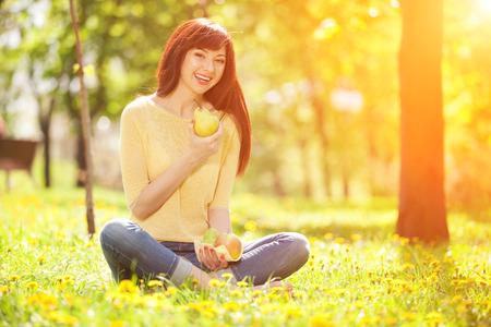 eating fruits: Mujer feliz que come las frutas en el parque