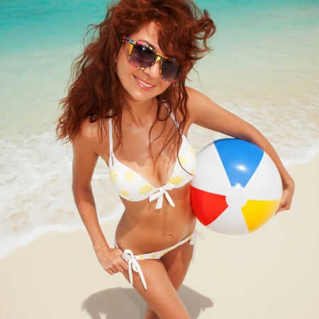Fun woman with ball on the beach background photo