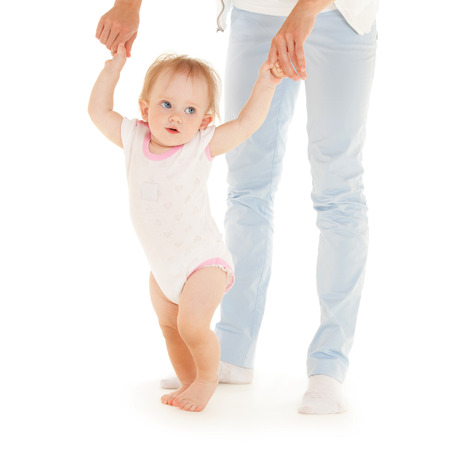Mother with daughter on the white background  First steps  photo
