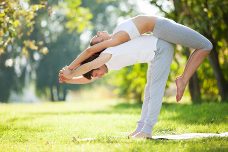 yoga man: Couple Yoga, man and woman doing yoga exercises in the park