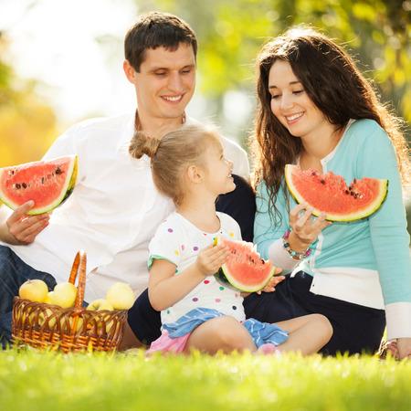 family happy: La familia feliz con un picnic en el jardín del otoño Foto de archivo