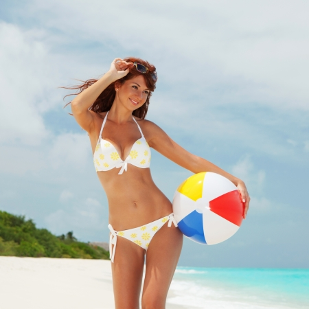 Young pretty woman with ball on the beach background photo