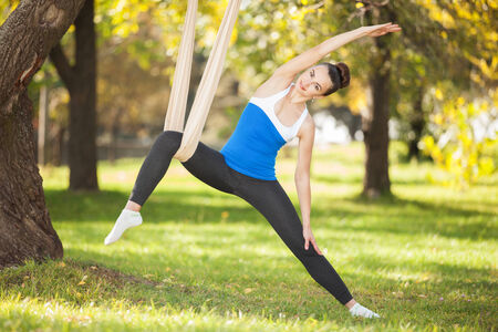 Anti-gravity Yoga, woman doing yoga exercises in the park photo