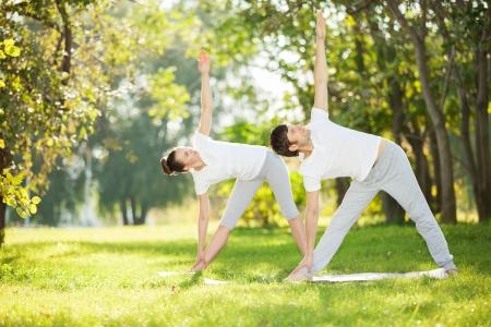 Couple Yoga, homme et femme faisant des exercices de yoga dans le parc