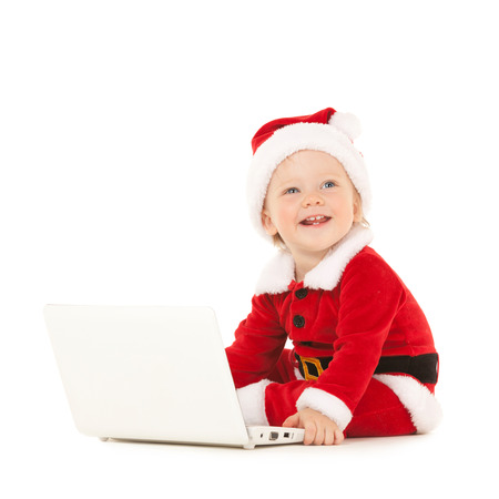 Cute santa baby with laptop on the white background photo