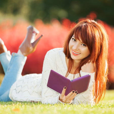 Young pretty woman with tablet in the park Stock Photo - 23837816