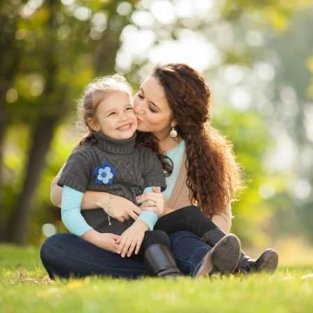 fall fun: Mother kissing her daughter in the park