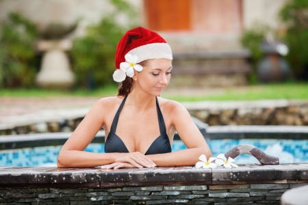 Beautiful woman with santa hat relaxing in jacuzzi at spa center photo