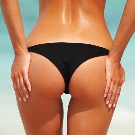 Sexy woman buttocks on the beach background photo