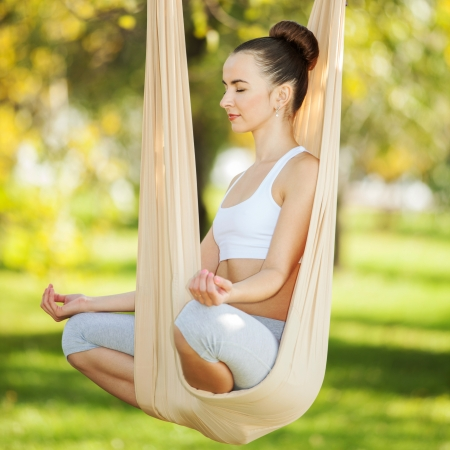 Anti-gravity Yoga, woman doing yoga exercises in the park Stock Photo